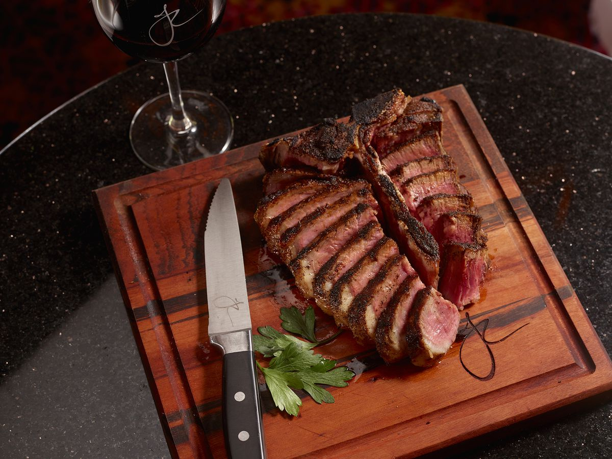 A steak, sliced on a cutting board, beside a knife, herbs, and a glass of wine