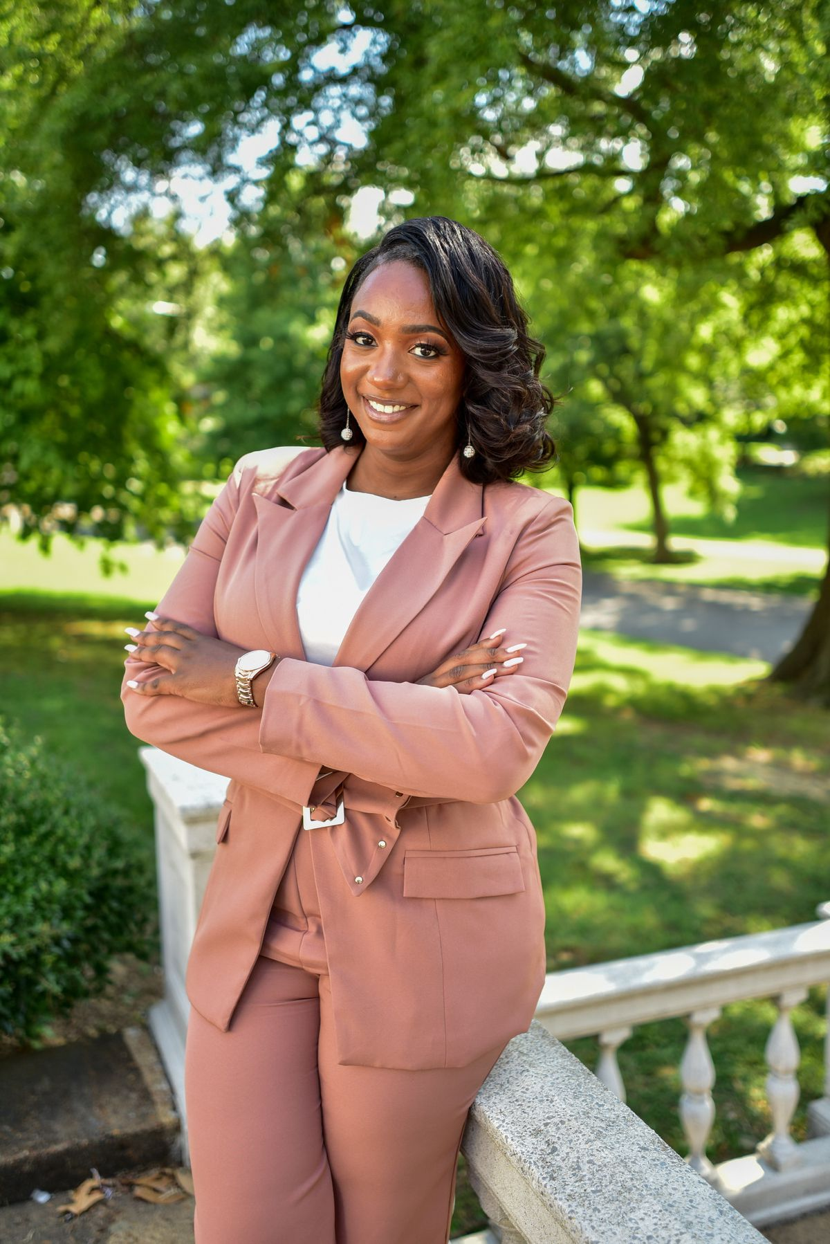 Tennessee Representative London Lamar smiles for a portrait outdoors with her arms crossed.