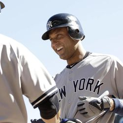 New York Yankees' Derek Jeter, right, is congratulated by Eric Chavez after he scored on a single by Nick Swisher off Minnesota Twins pitcher Brian Duensing  in the third inning of a baseball game Wednesday, Sept. 26, 2012 in Minneapolis.