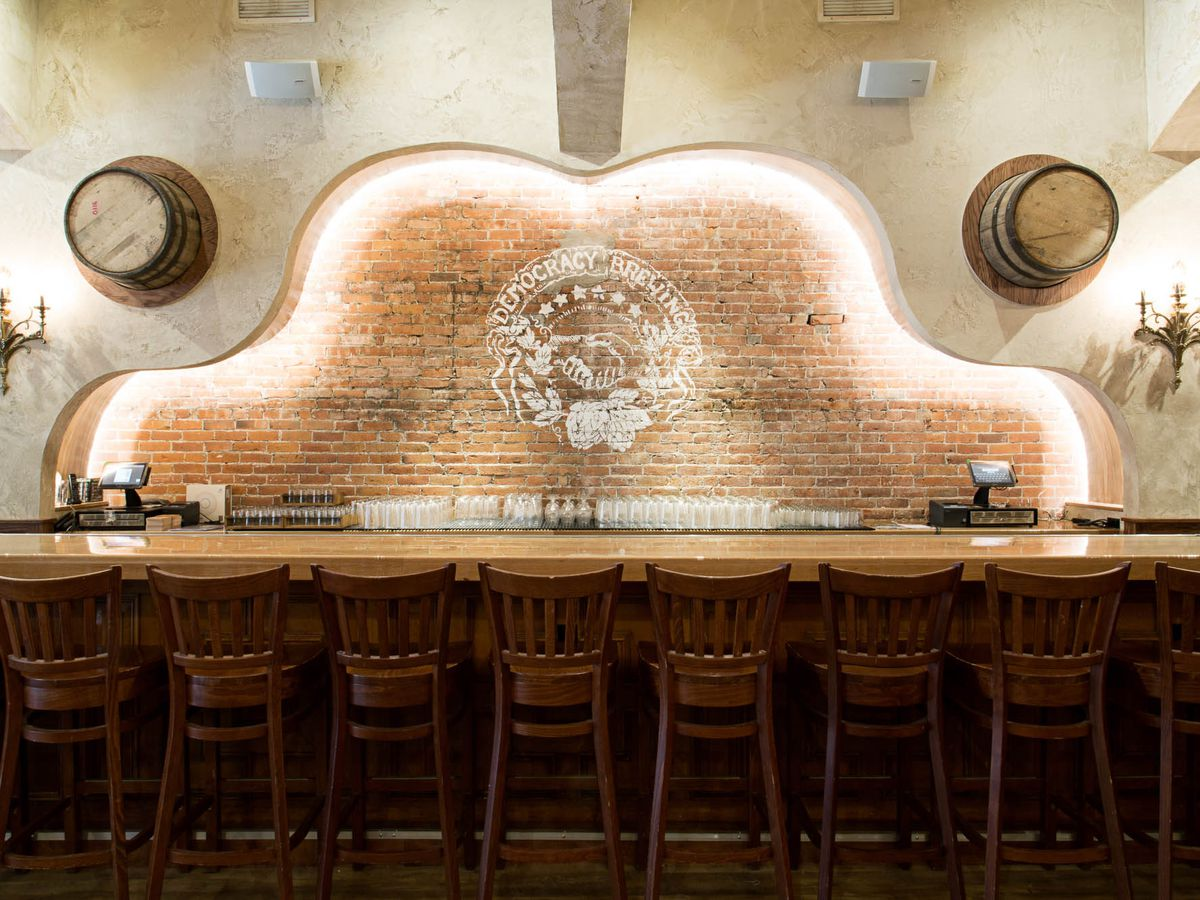 """A wooden bar with an illuminated brick wall in the rear and two half barrels hanging overhead. A logo painted on the wall reads """"democracy brewing"""""""