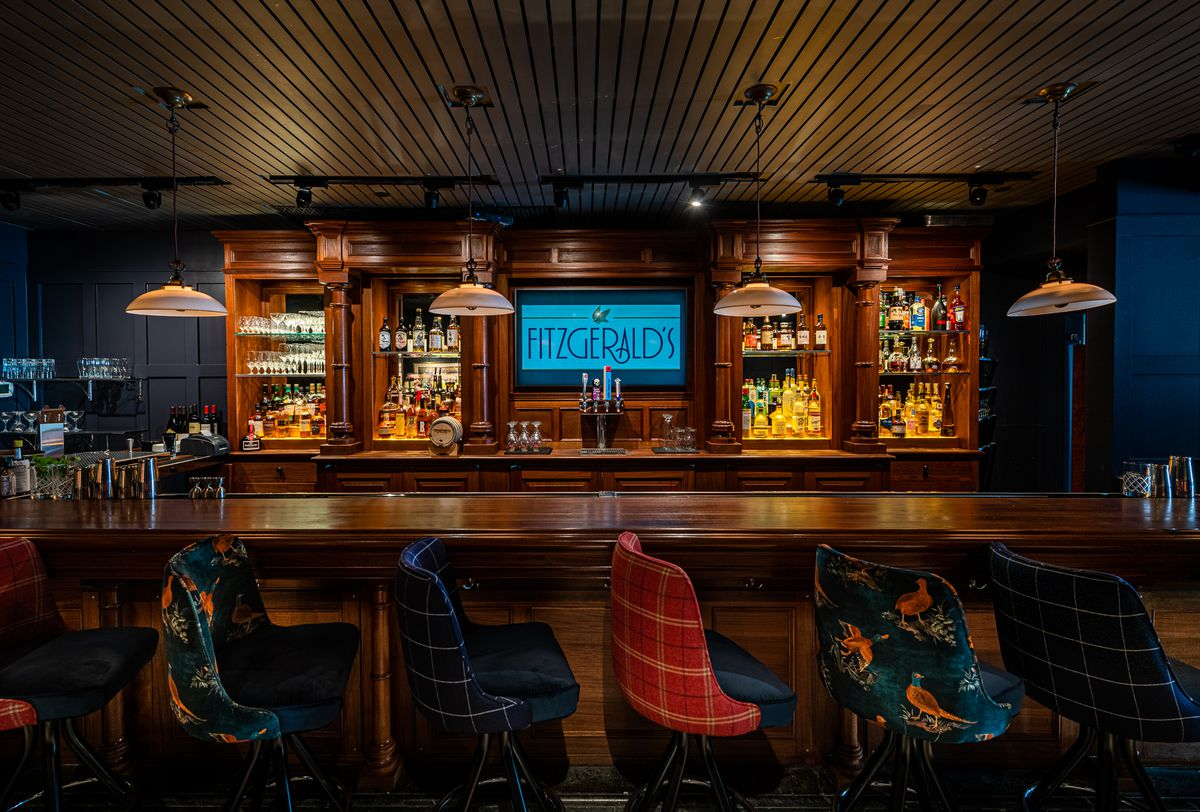 The mahogany bar at Fitzgerald's features 12 mix-and-match stools upholstered in preppy plaids and hunting lodge patterns of ducks flying across velvet