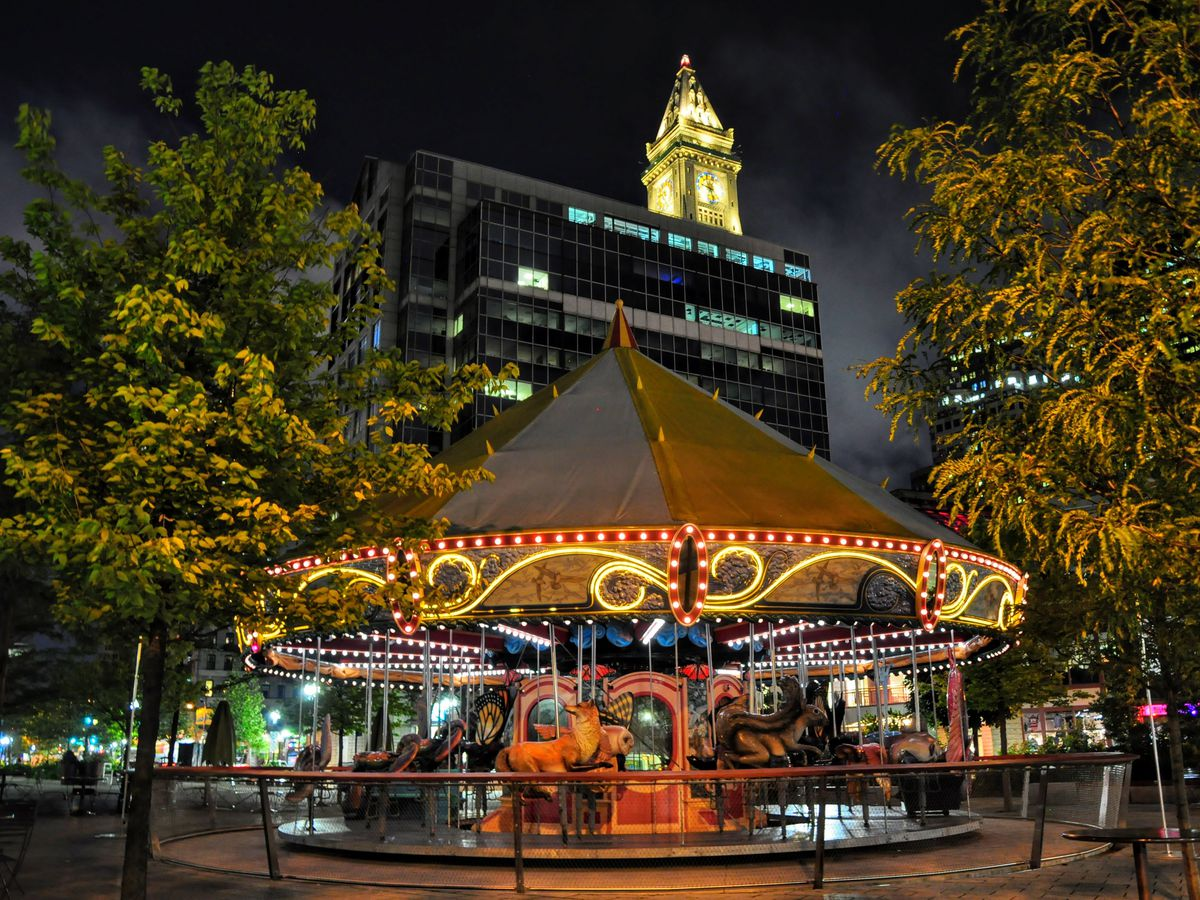 A carousel lighted up at night in a city park.