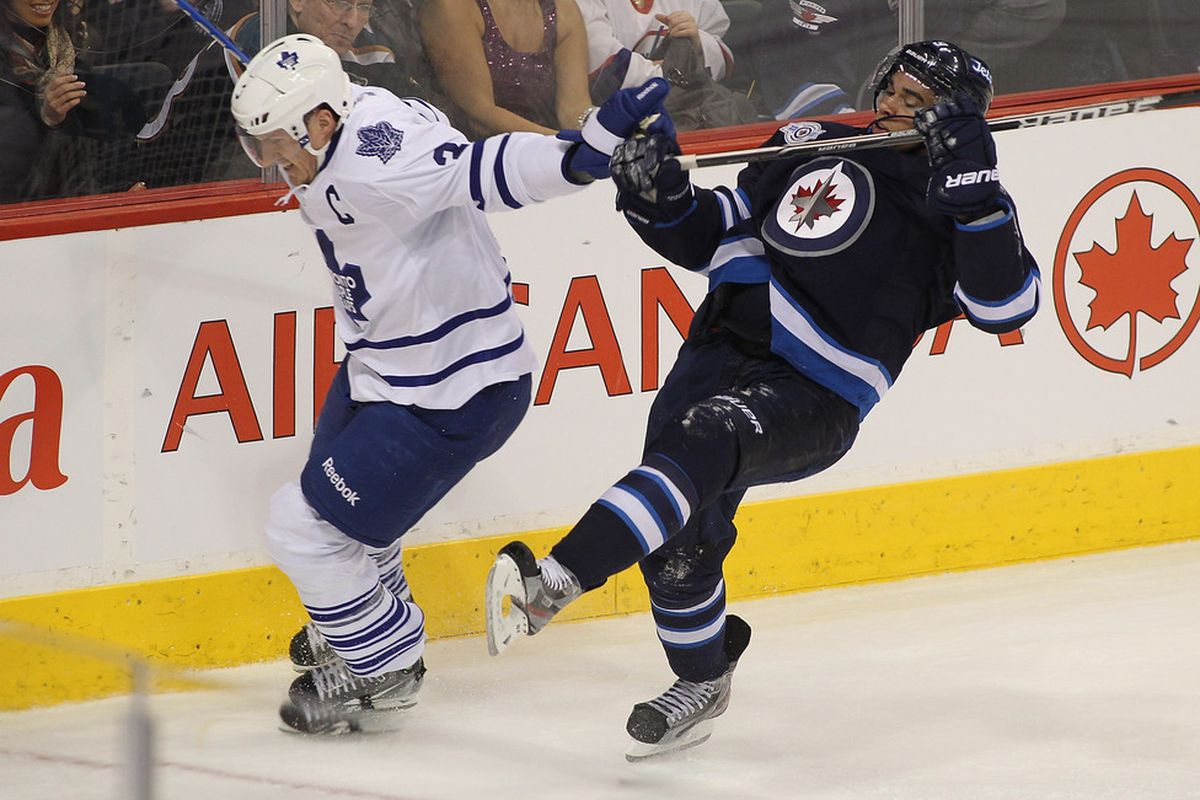 WINNIPEG, CANADA - DECEMBER 31: Dion Phaneuf #3 of the Toronto Maple Leafs collides with Evander Kane #9 of the Winnipeg Jets in NHL action at the MTS Centre on December 31, 2011 in Winnipeg, Manitoba, Canada. (Photo by Marianne Helm/Getty Images)