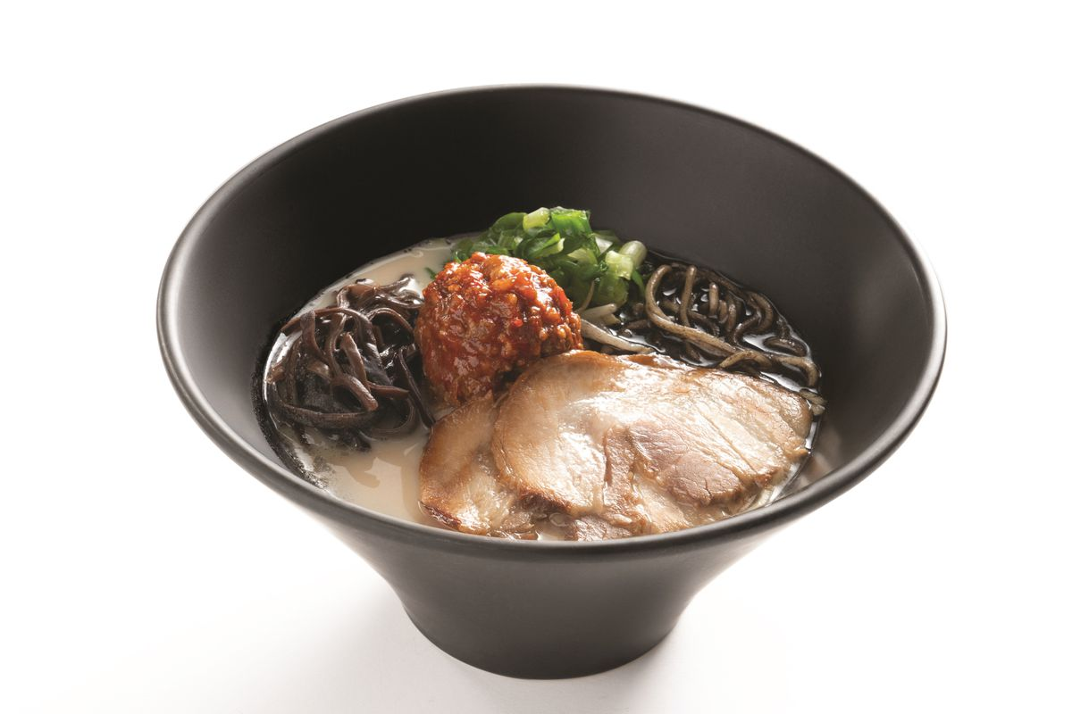 Bowl of ramen with pork belly, spices, green onion, and broth in a dark bowl.