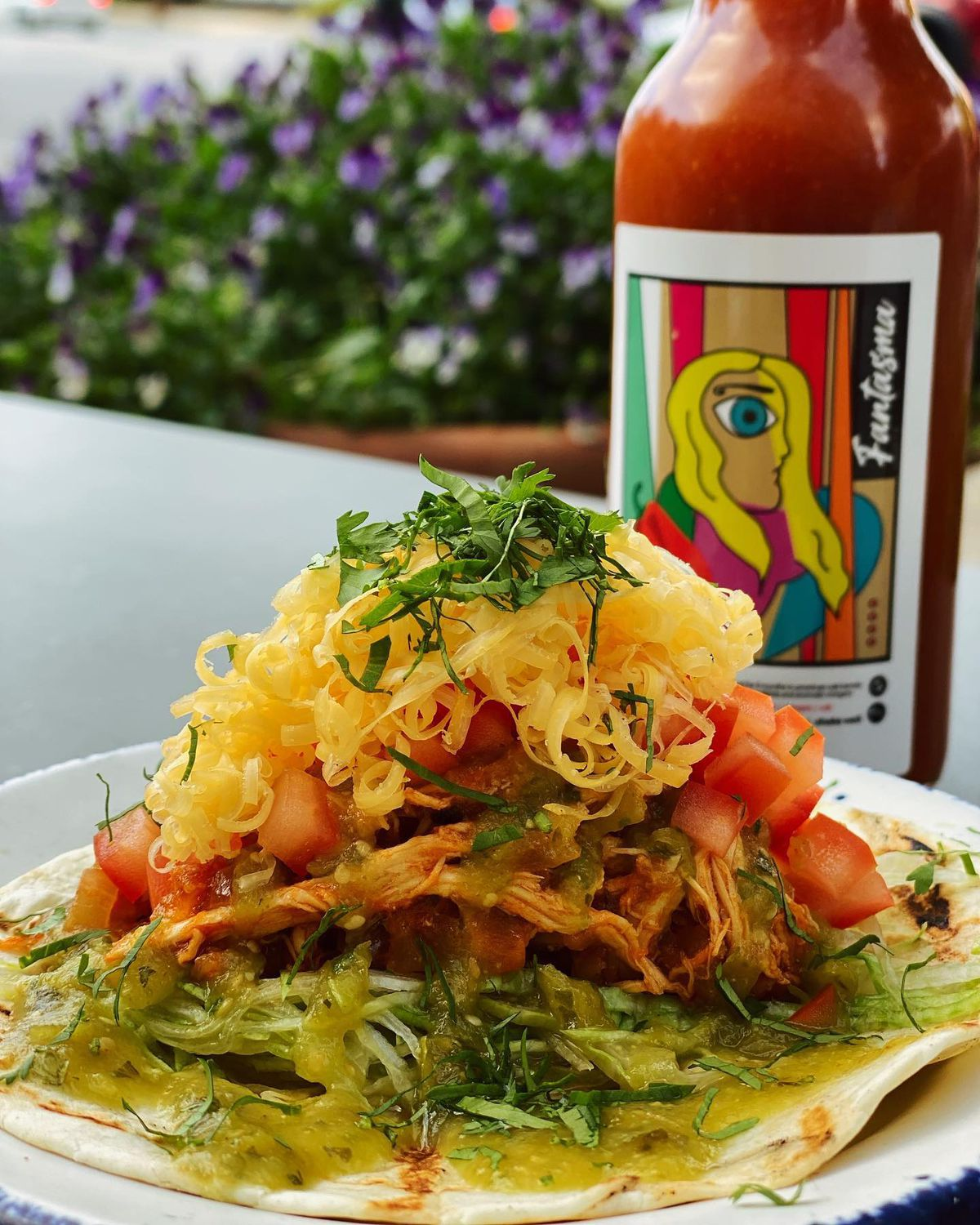 Chicken tinga topped with shredded cheese, chives, and chopped tomatoes sits atop a flour tortilla with a bottle of hot sauce in the background.