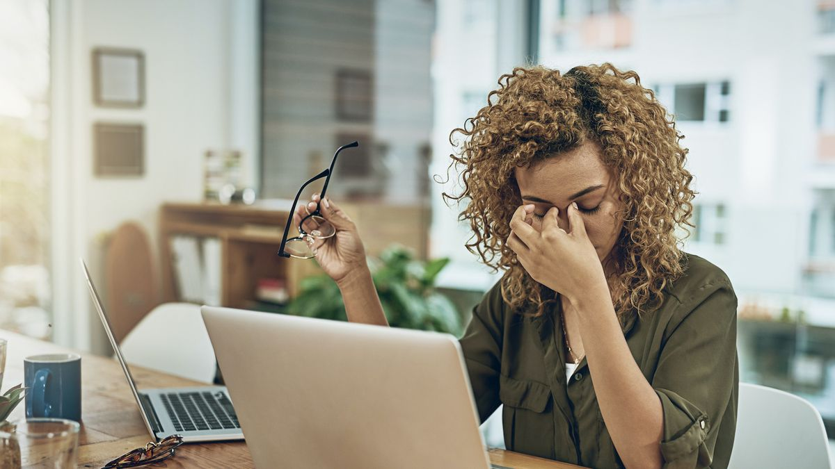 A stressed out teacher sitting at her laptop rubs her eyes.