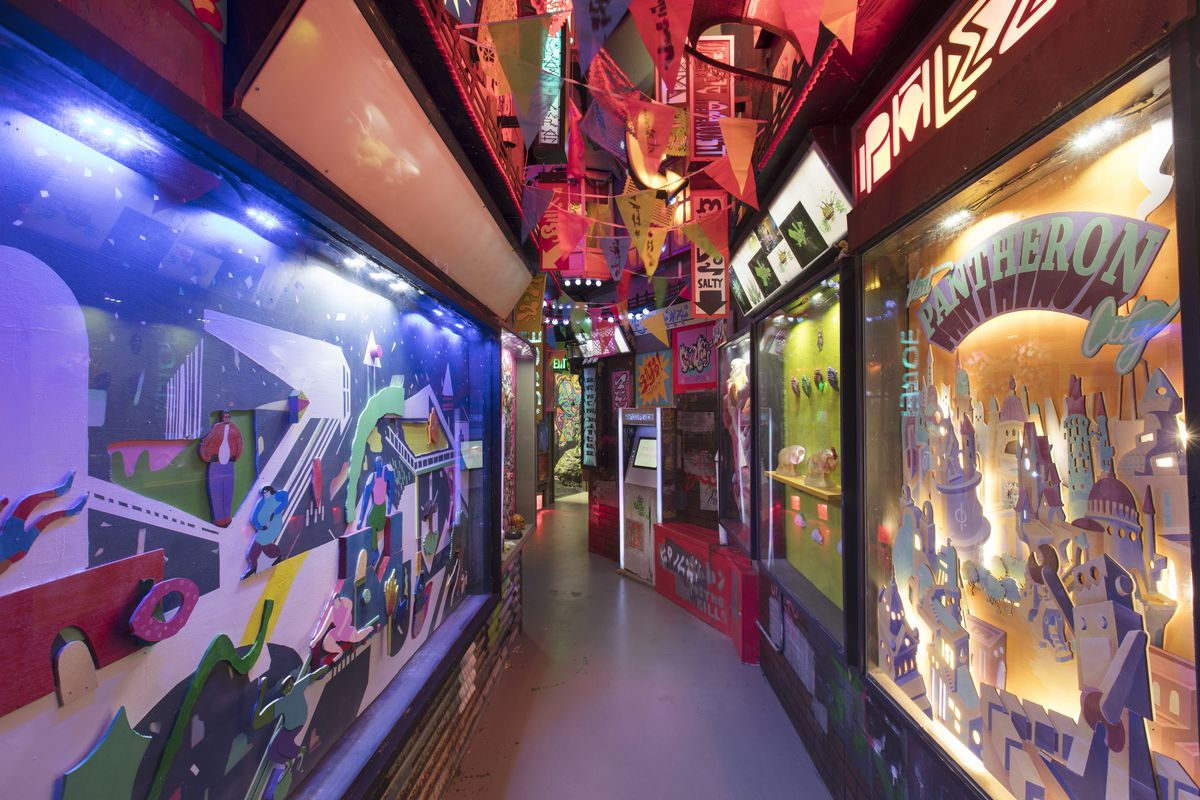 A hallway with installations and video games inside Meow Wolf's House of Eternal Returns.