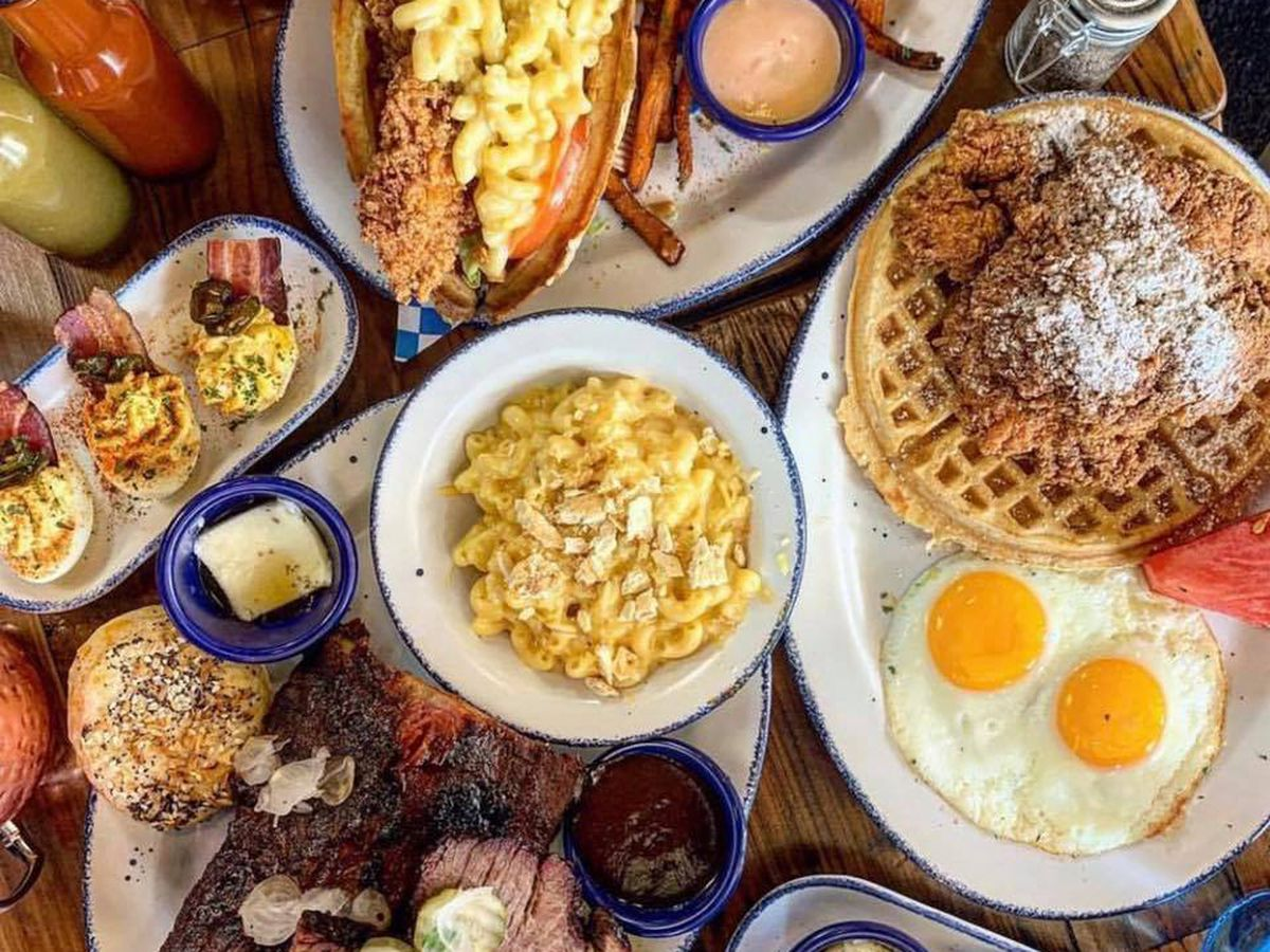 An overhead view of chicken and waffles, macaroni and cheese, deviled eggs, over-easy eggs, and more