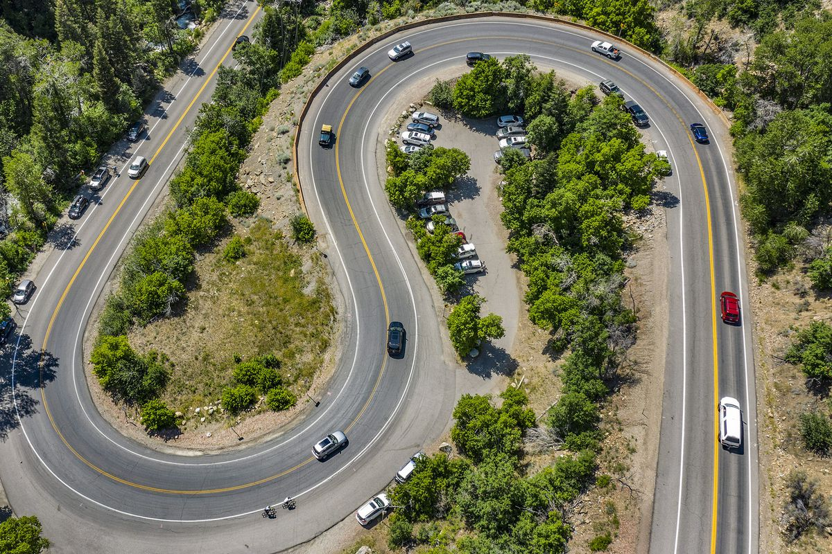 """Motorists share the road with cyclists as they negotiate the S-curve in Big Cottonwood Canyon on Friday, July 17, 2020. The Utah Department of Transportation, working with Panasonic, has deployed a network of next-generation radio pods along select Utah highway corridors, including Big Cottonwood Canyon, that have the ability to """"communicate"""" with emerging smart vehicle technology. The pods can gather metrics from passing vehicles, process the information and send out important information like warning drivers of unsafe conditions, road closures due to accidents or, potentially, even road hazards like potholes or rocks in the road."""