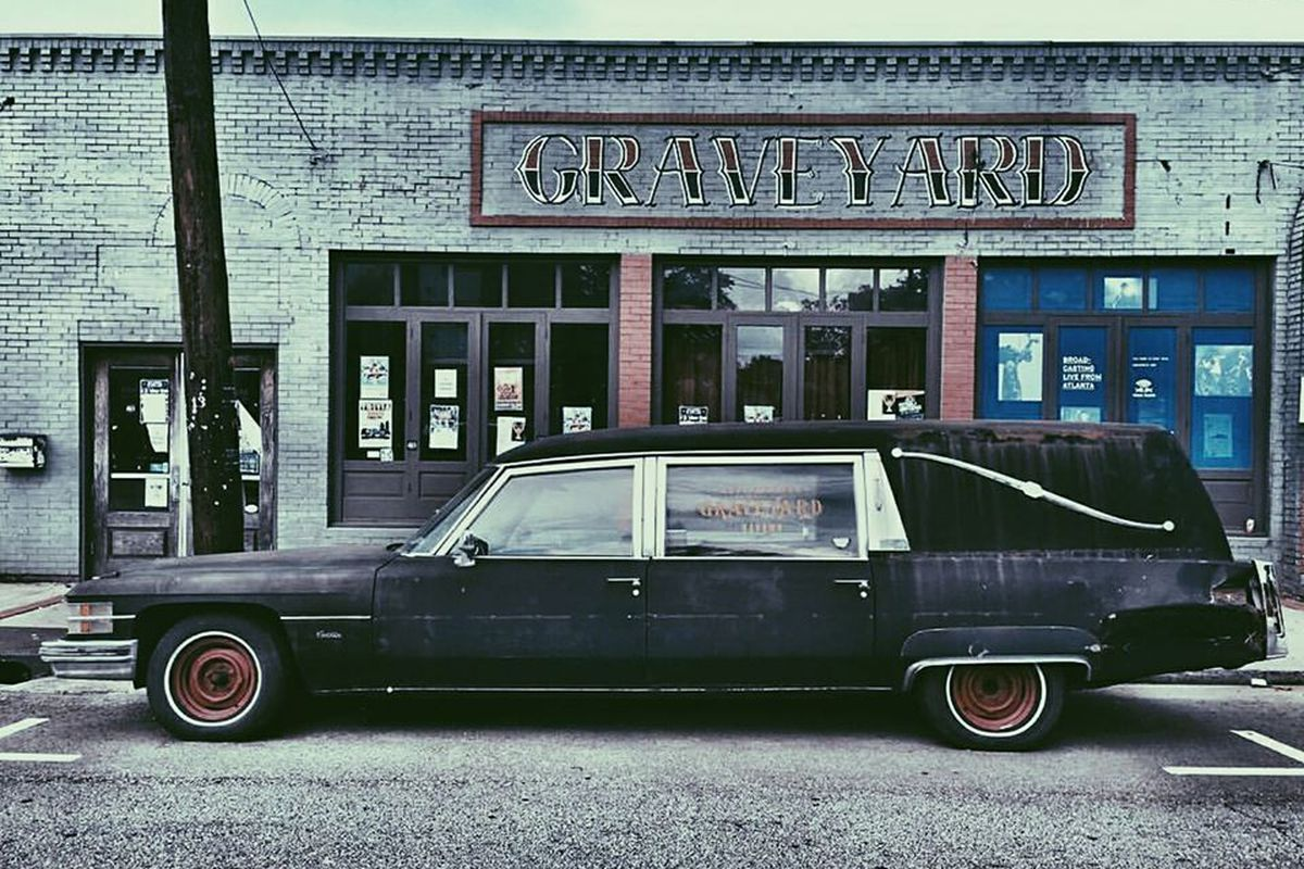 A cadillac black hearse parked in front of Graveyard Tavern in East ATlatna Village