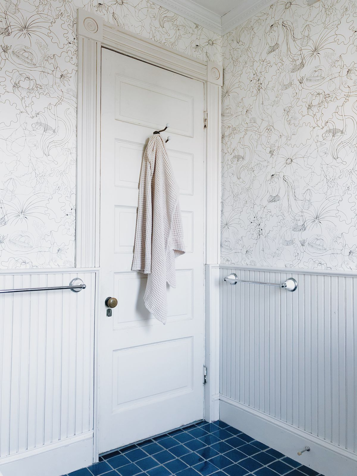 New minimalist white wallpaper covers the wall of the bathroom, which has beaded boarded paneling and royal blue tile.
