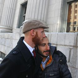 Derek Kitchen, left, and his partner Moudi Sbeity hug following court on Wednesday, Dec. 4, 2013, outside Frank E. Moss United States Courthouse, in Salt Lake City. A challenge to Utah's same-sex marriage ban by three gay couples was back in court Wednesday as a federal court judge heard arguments in the case. Kitchen and Sbeity are plaintiff's in this case.