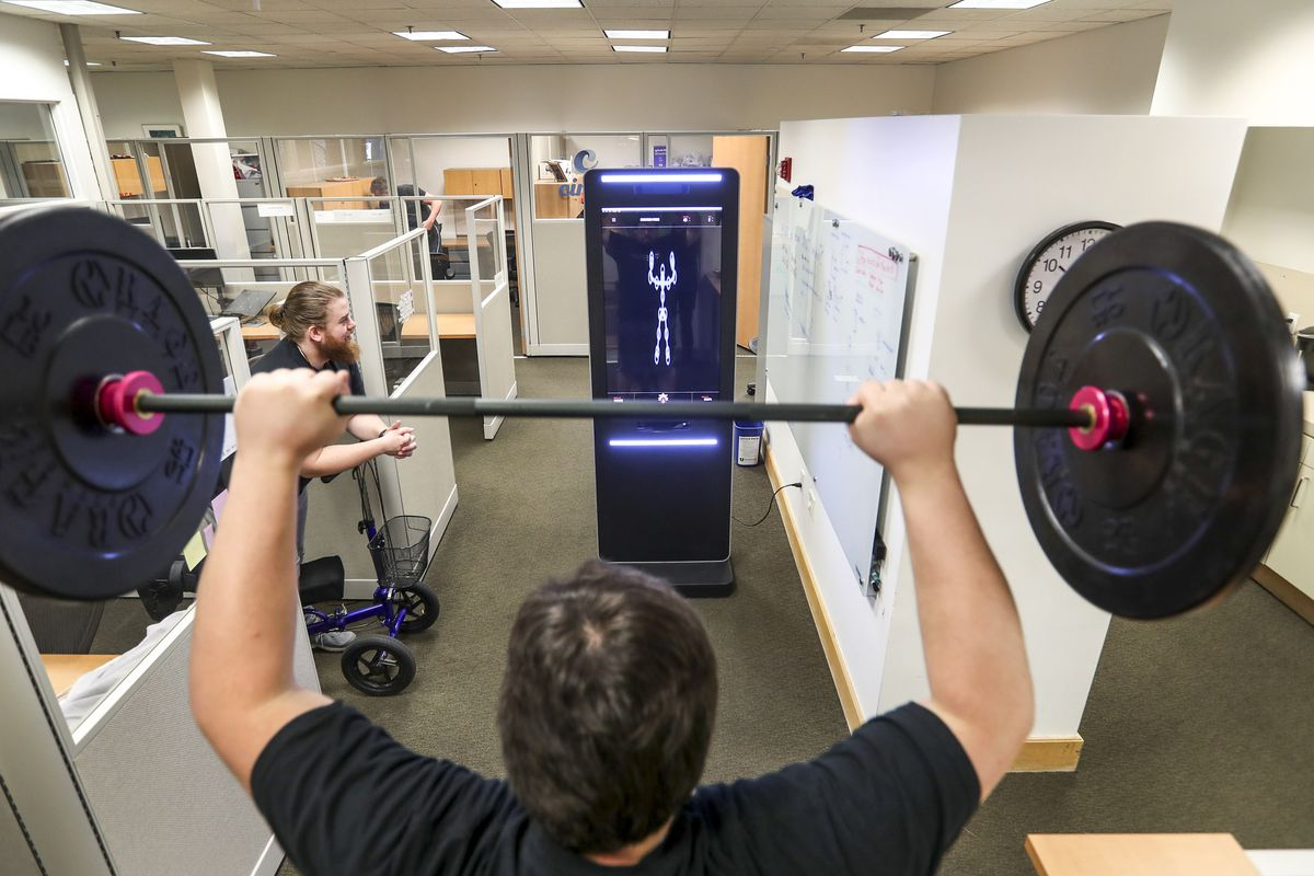 "True Adherence co-founder Chris Bright, front, performs a standing press in front of the company's smart workout system as co-founder Kyle Poulin watches his form during a demonstration at the University of Utah in Salt Lake City on Thursday, Feb. 13, 2020. The system features video cameras and software processing that acts as a fitness ""coach,"" correcting for form and function."