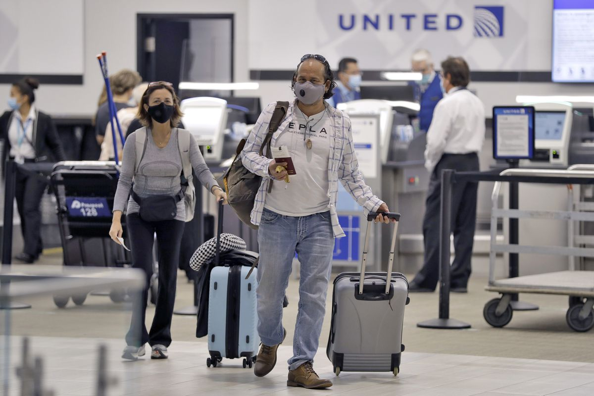 Two passengers wearing face masks and pulling their suitcases walk away from a United Airlines ticket counter on June 16 in Tampa, Florida. Airline travel is still down significantly and United is considering furloughing 36,000 employees.