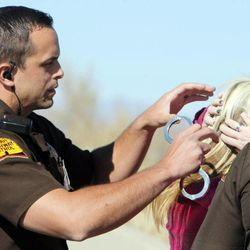 Utah Highway Patrol trooper Mike Singleton puts handcuffs on a woman after a roadside sobriety test Wednesday, Oct. 17, 2012, on Bangerter Highway near 1300 South.