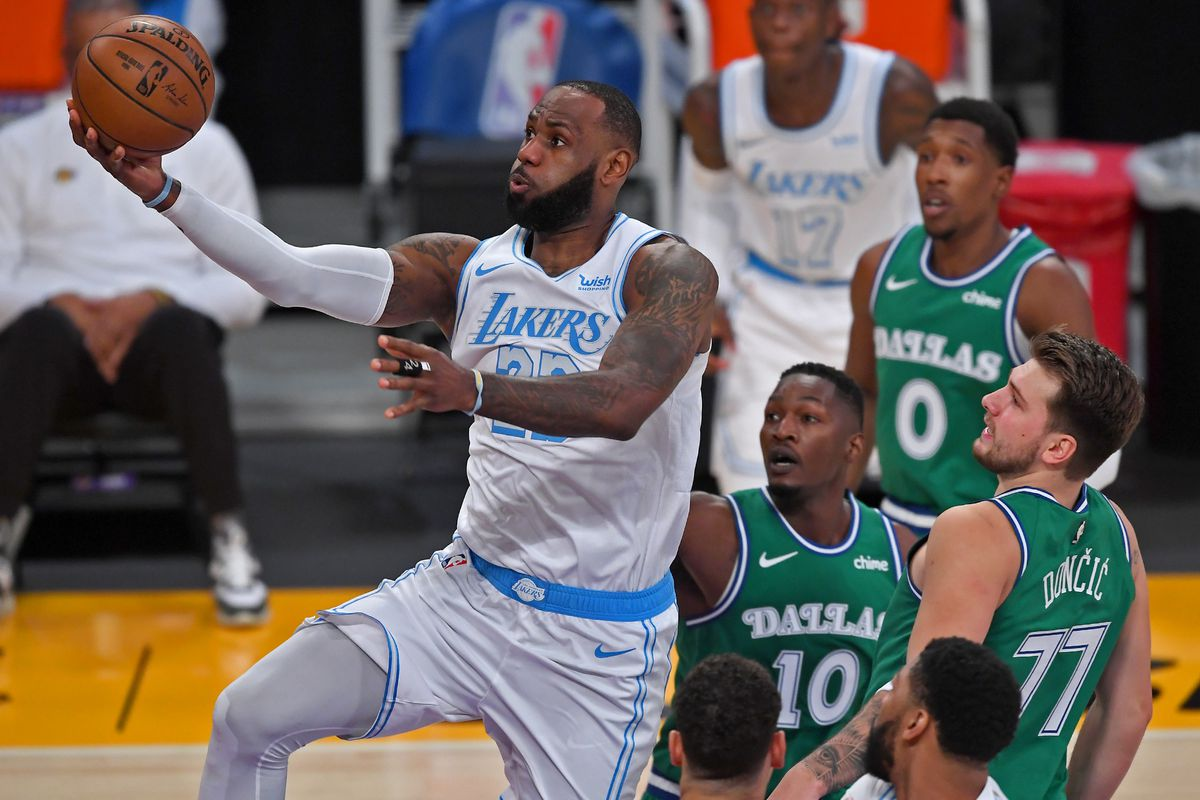 Los Angeles Lakers forward LeBron James drives past Dallas Mavericks forward Dorian Finney-Smith  and Dallas Mavericks guard Luka Doncic for a basket in the first quarter of the game at Staples Center.