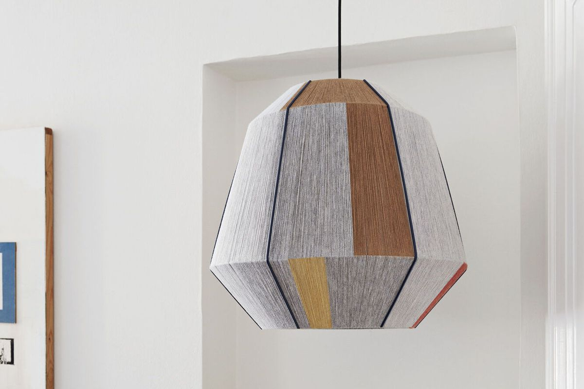 A lamp with woven yarn around its frame.
