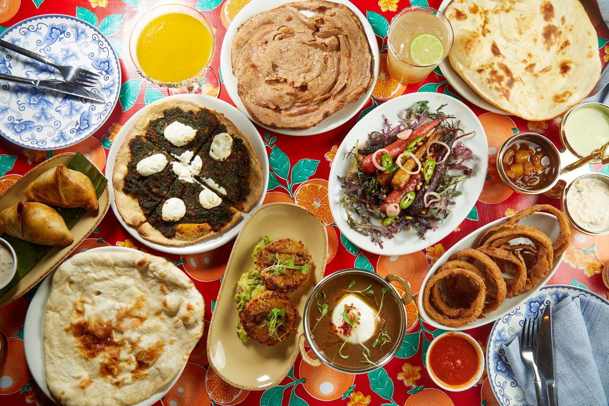 A spread of food at Bombay Bread Bar on a colorful, red floral tablecloth.
