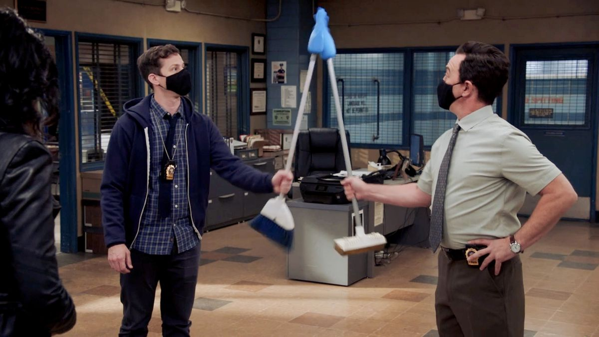 Jake and Boyle use two brooms with rubber gloves at the end to high five.