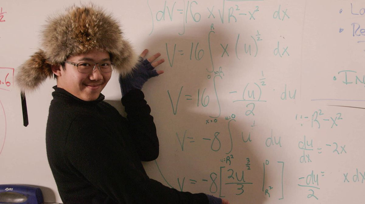 A teenager in a fuzzy cap stands in front of a whiteboard gesturing with a smile at calculus equations.