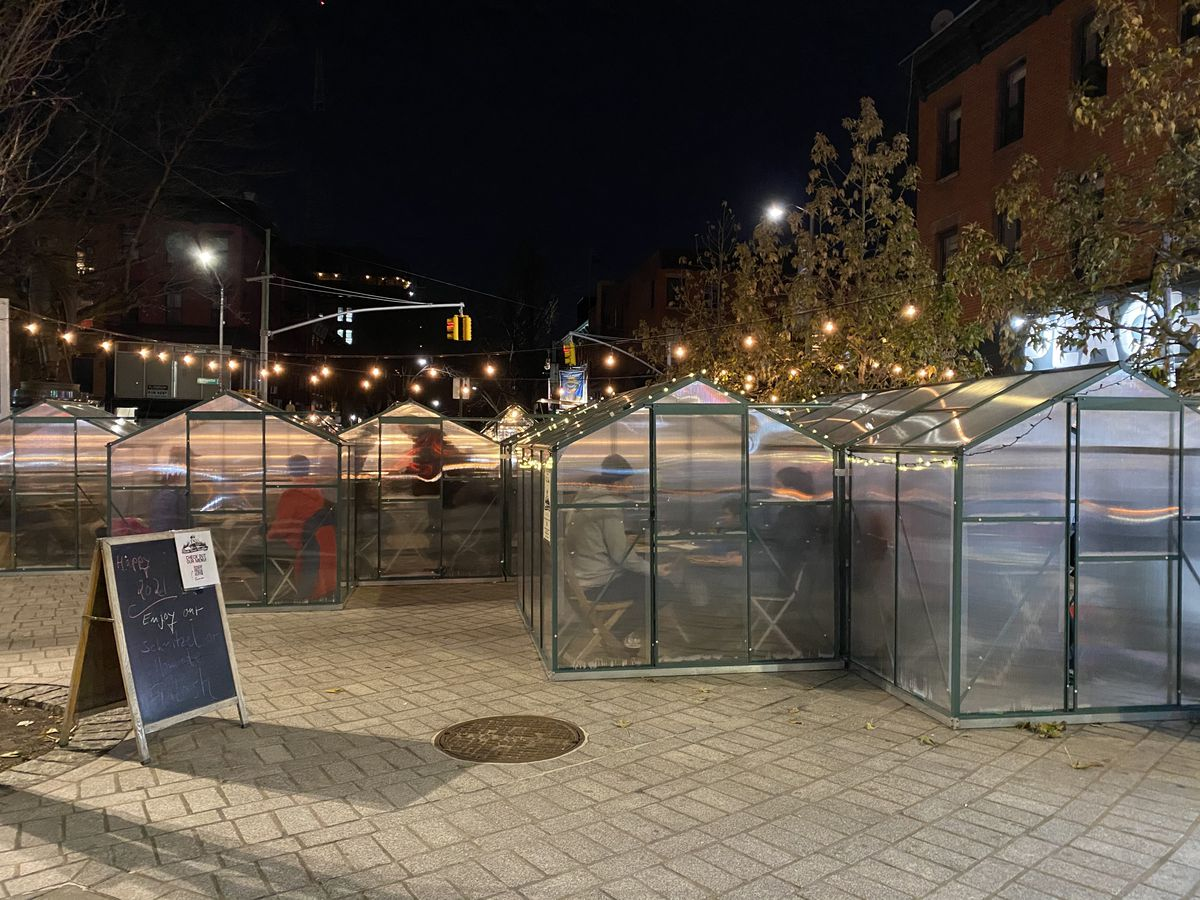 Glass cabins with two-top tables positioned inside arranged on a public plaza
