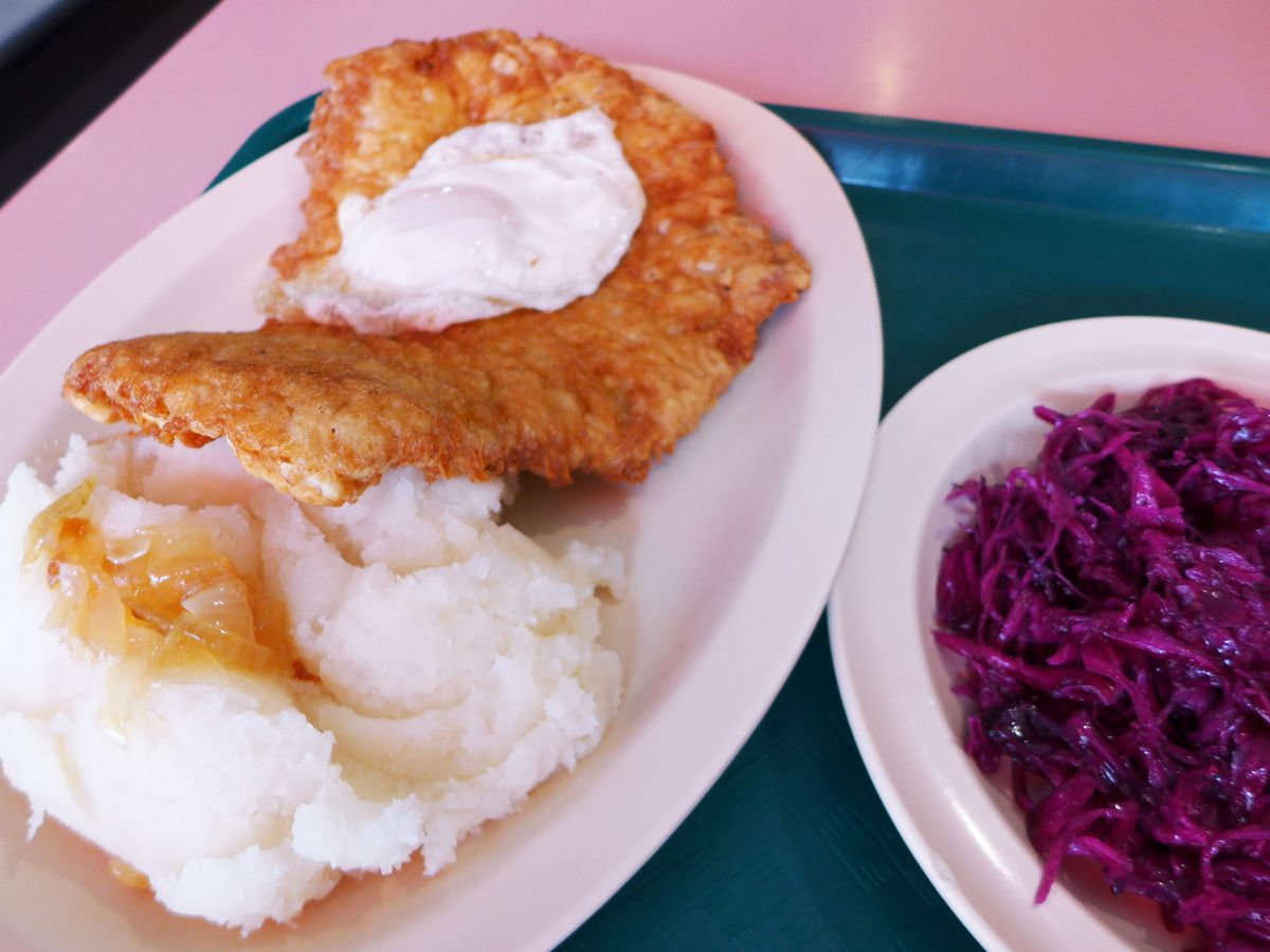 A well browned veal schnitzel with an egg on top, and mashed potatoes and purple cabbage on the side...