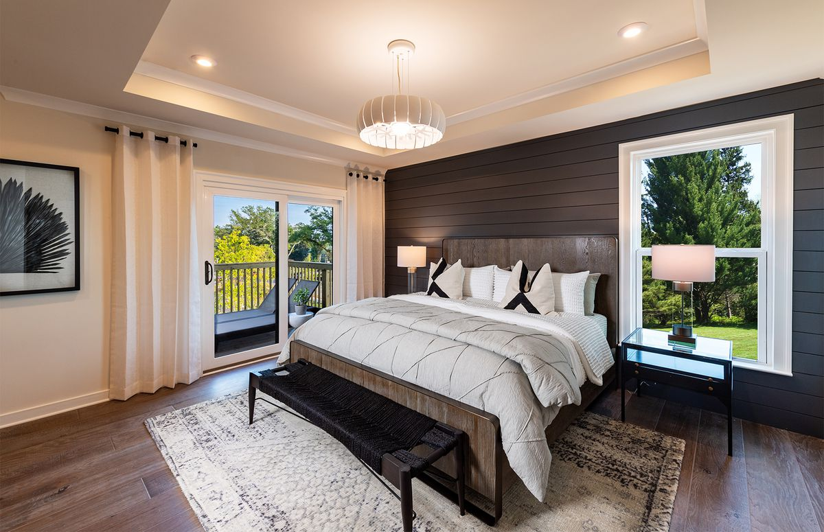 A master bedroom with a king-size bed with wooden headboards, seated between a window and a glass door, both looking out at green trees.