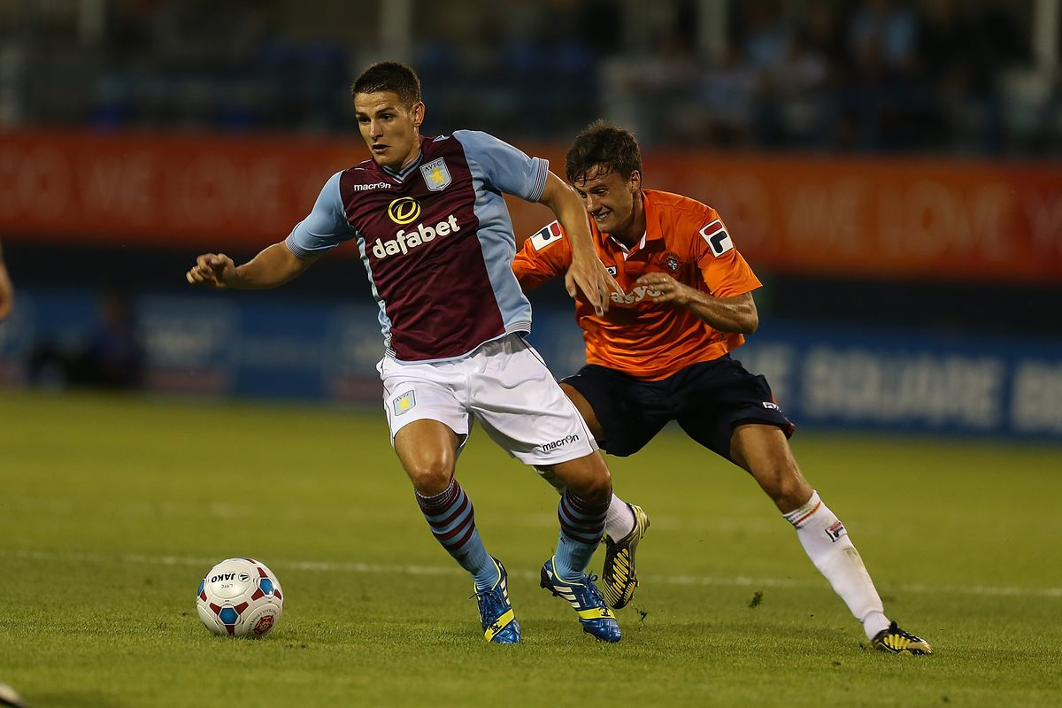Ashley Westwood of Aston Villa looks to play the ball watched by Jonathan Smith of Luton Town during the Pre Season Friendly match between Luton Town and Aston Villa at Kenilworth Road on July 23, 2013 in Luton, England.