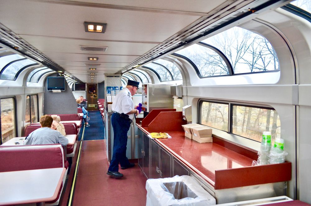 A train car wrapped with windows is filled with a few people and a conductor who is cleaning a coffee machine.