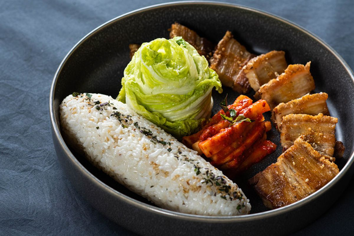 A view of Korean pork belly, with cabbage and a cylinder of seasoned rice on the side