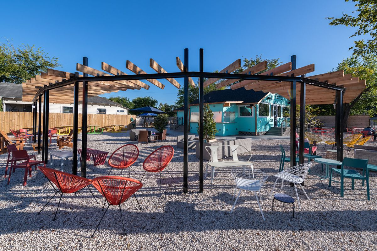 a gravel patio with a pergola and colorful outdoor chairs