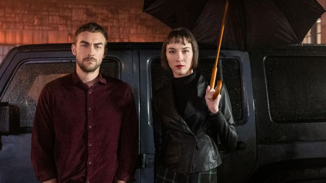 Tom Austen and Sydney Lemmon stand in front of a black van and glower as Daimon and Ana Helstrom in Helstrom