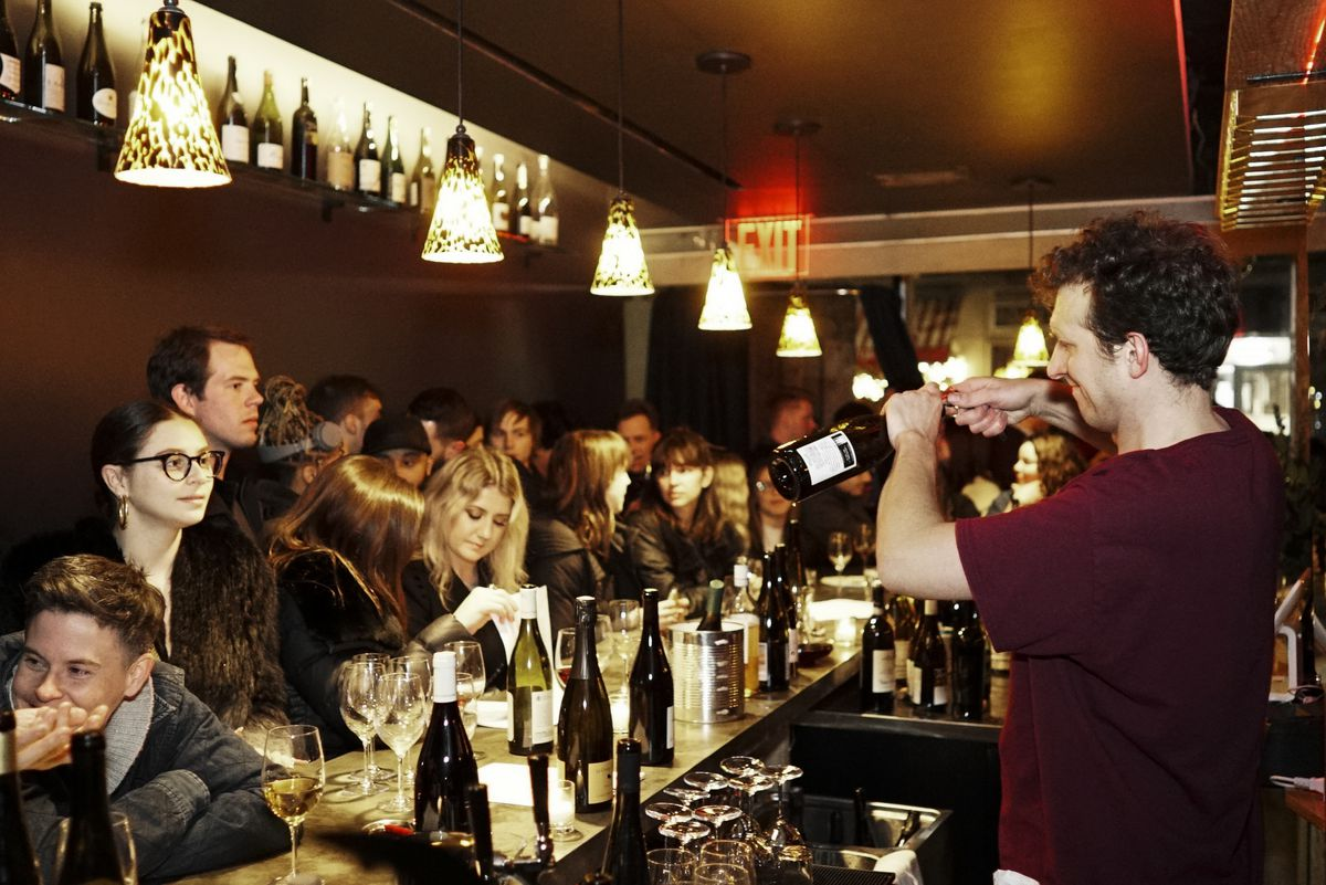 A bar packed with people, with a bartender uncorking a wine.