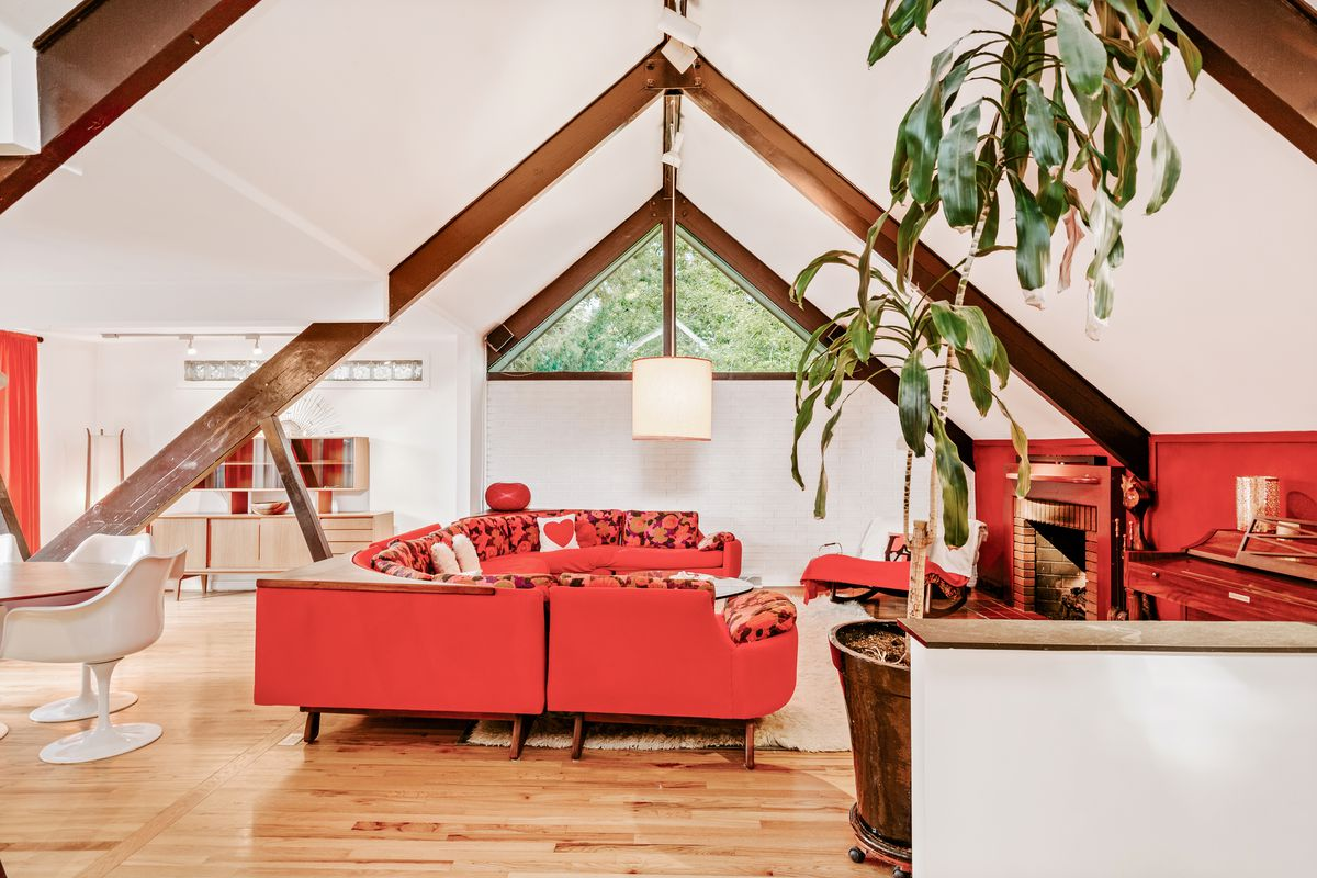 An A-frame living roof features white ceilings with exposed brown beams, red couches, and wood floors.
