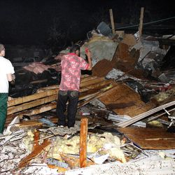 Two men look for people who may be trapped underneath rubble at Pinaire Mobile Home Park after it was struck by a reported tornado, in Wichita, Kan., Saturday night, April 14, 2012.