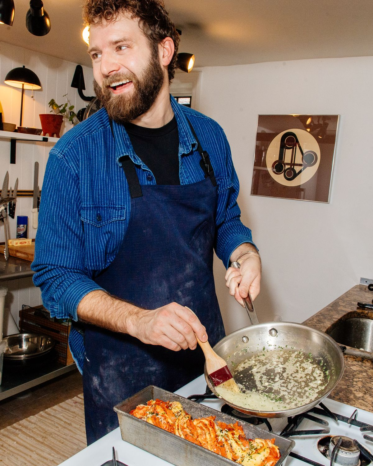 Bearded man wearing apron smiles while brushing butter from a pan in a kitchen.