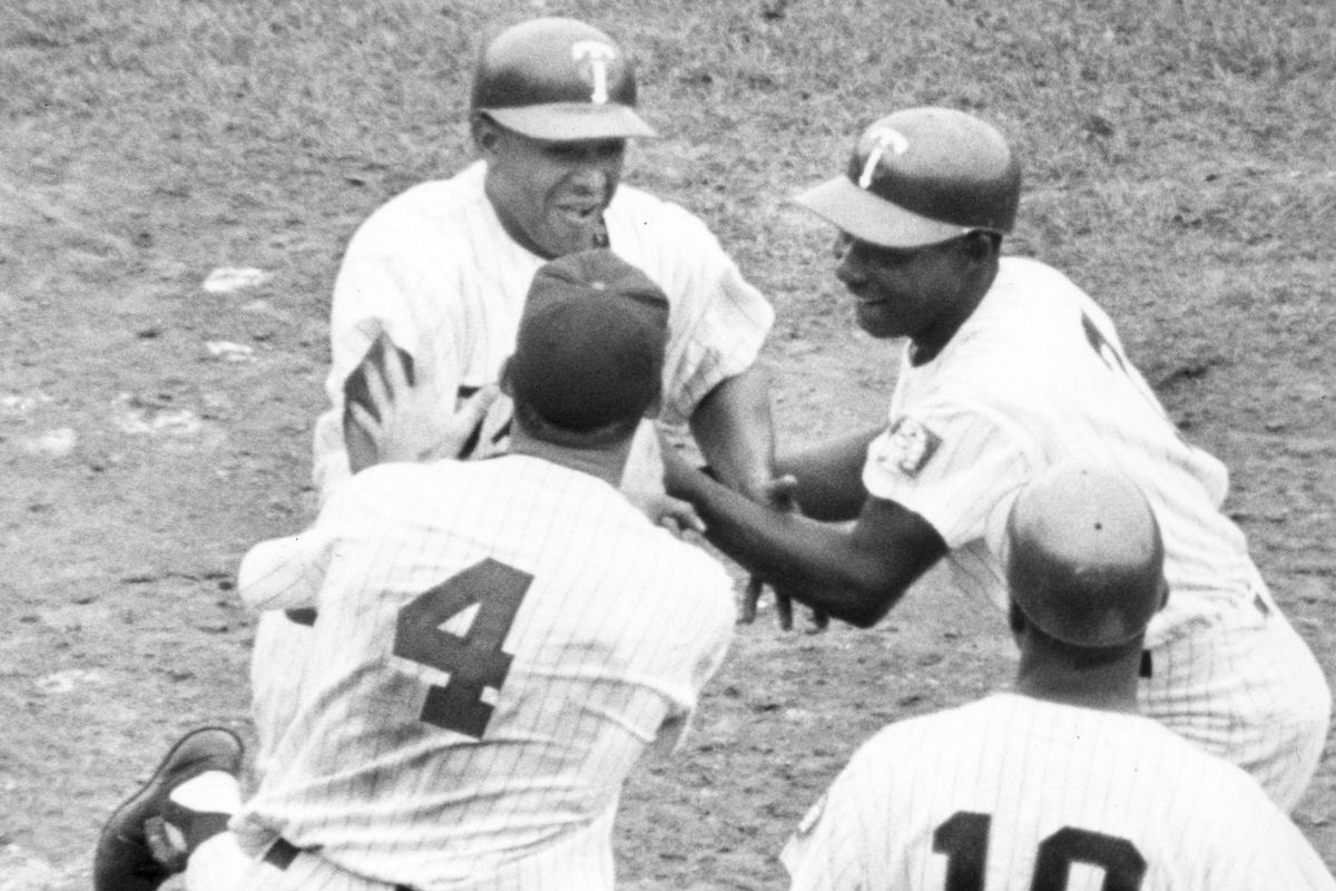 Minnesota Twins Julio Becquer is greeted by teammates Bob Allison(4) and Earl Battey(10) and Lenny Green after Becquer's 7/4/61 Grand Slam. Minneapolis Tribune photo by staff photographer John Croft.