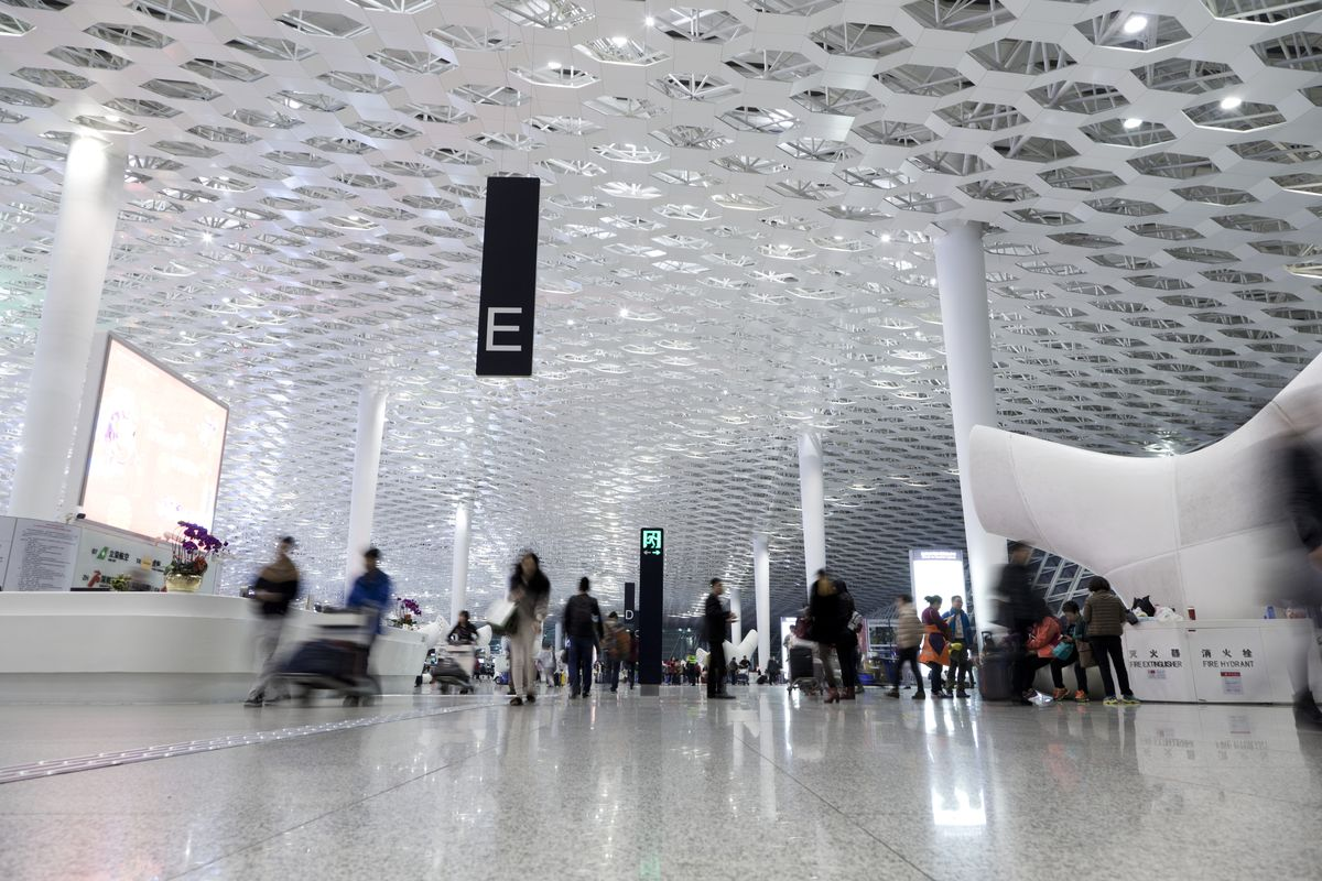 The interior of the Shenzhen Bao'an International Airport in China. The interior is white and the ceiling has a honeycomb design.