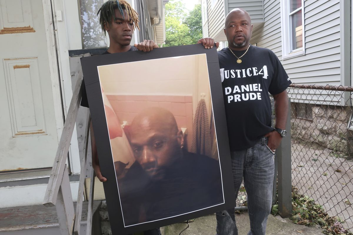 """In this Sept. 3, 2020, file photo, Joe Prude, brother of Daniel Prude, right, and his son Armin, stand with a picture of Daniel Prude in Rochester, N.Y. Daniel Prude, 41, suffocated after police in Rochester put a """"spit hood"""" over his head while he was being taken into custody. He died March 30, after he was taken off life support, seven days after the encounter with police."""