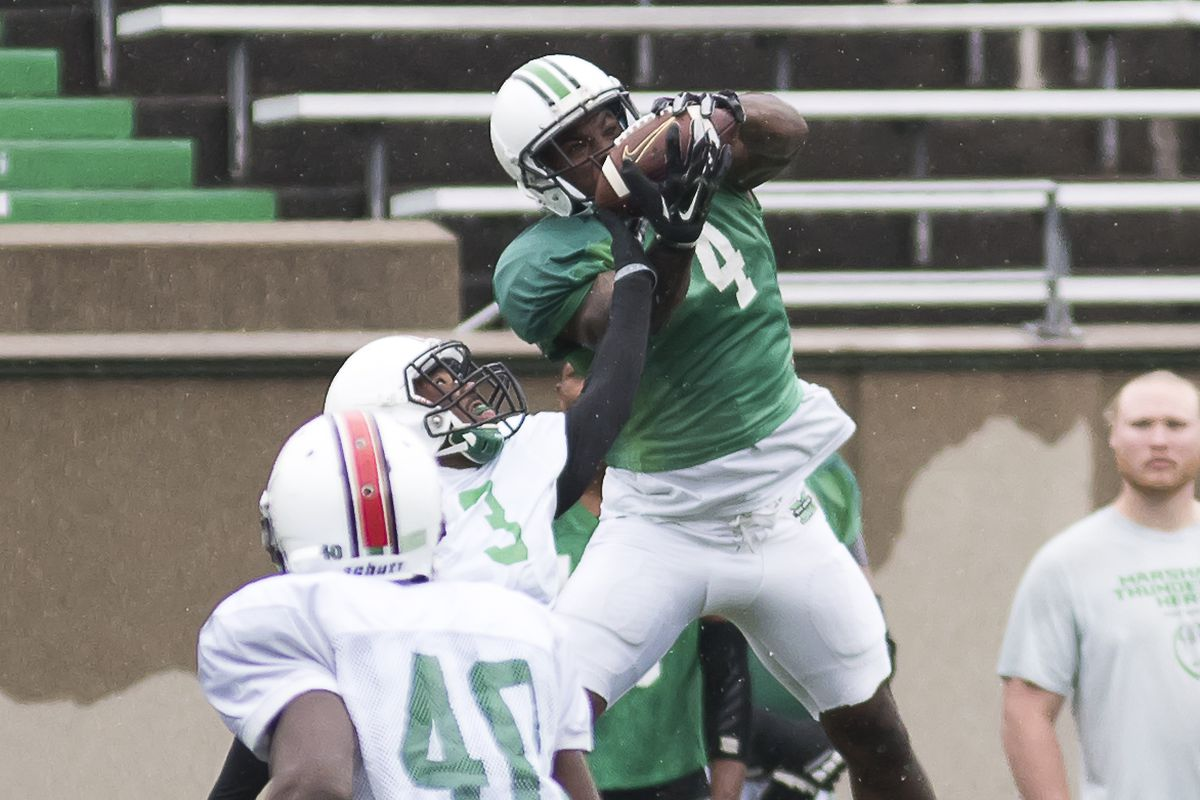 Deon-Tay McManus (4) hauls in a reception over Chris Jackson (3) in the annual Green & White Game.