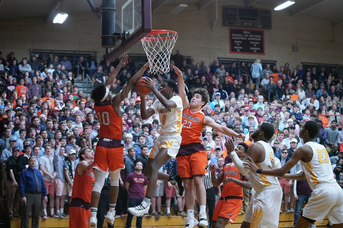 Simeon's Antonio Reeves (3) slices between Brother Rice's Jalen Rheams (10) and Anthony Arquilla (23).
