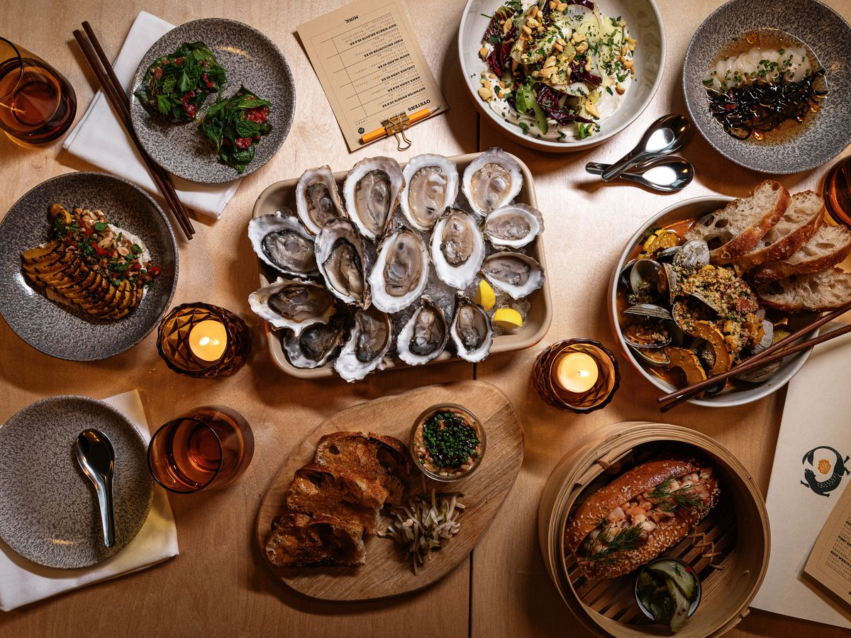 A spread of oysters, steamed clams, squash, shrimp rolls, and other items at Mink.