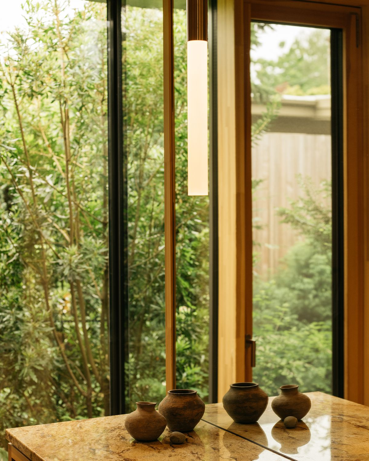 A desk with several clay objects.  Behind the desk is a floor-to-ceiling window with a view of lush trees and plants.