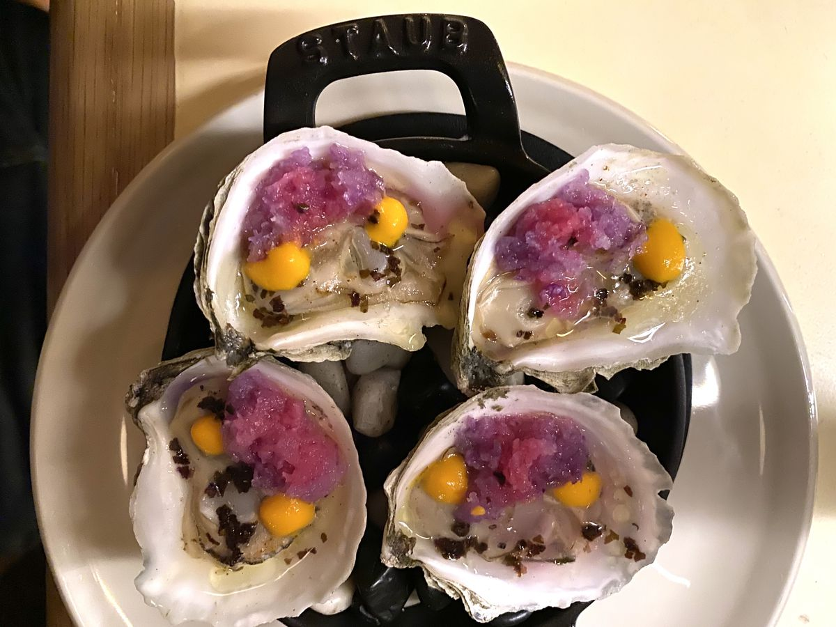 Four grilled oysters topped with purple daikon and orange aji dulce hot sauce sit atop a cast iron skillet at 232 Bleecker