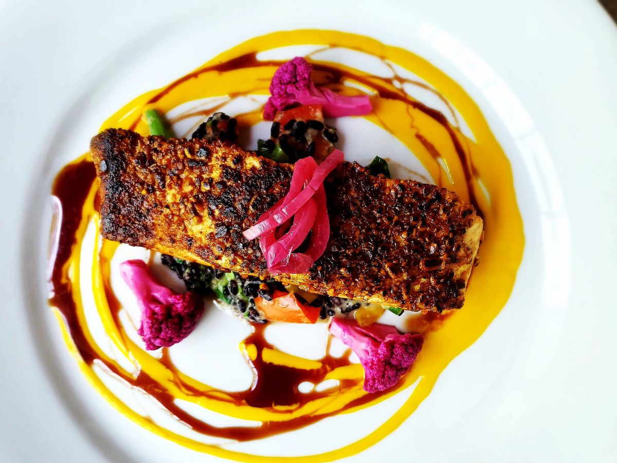 A charred piece of crusted salmon on a plate with sauce and vegetable fixings