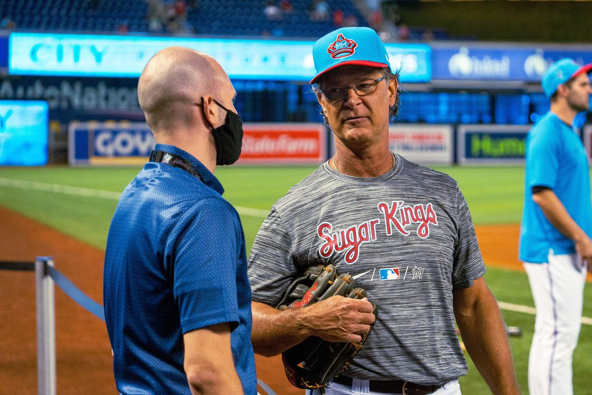 Marlins manager Don Mattingly chats with broadcaster Paul Severino during batting practice at LoanDepot Park