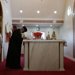 Rev. Joseph Boules, left, prays during a mass at St. Mary and St. Verena Orthodox Coptic Church in Anaheim, Calif., Wednesday, Sept. 19, 2012.