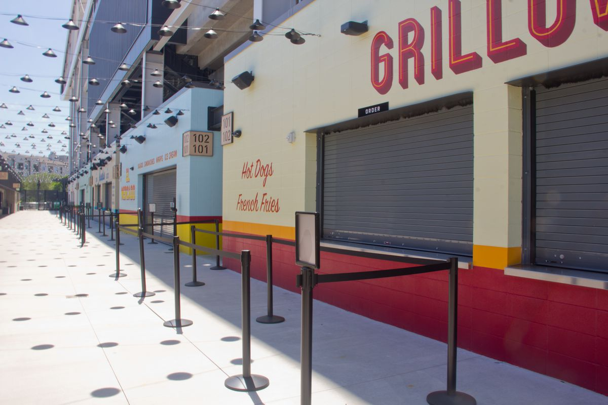 Colorful concession stand restaurants that are closed, with an alfresco hallway lined with hanging lights
