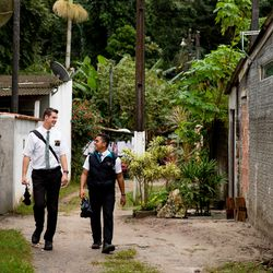Elders Tanner McKee and Pedro Cabral, missionaries for The Church of Jesus Christ of Latter-day Saints, walk a narrow street in Paranaguá, Brazil, on Saturday, June 1, 2019.