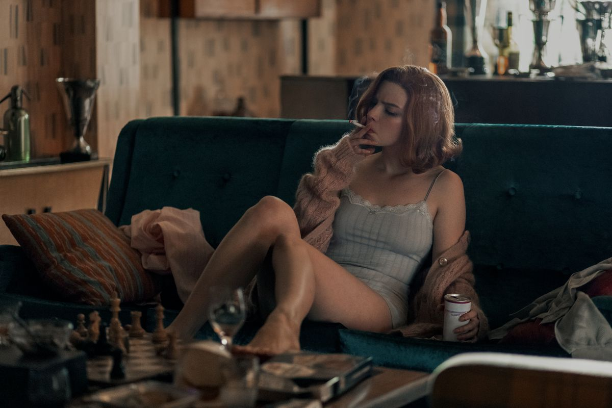 A thin redheaded woman smokes a cigarette, dressed in a camisole, underwear, and cardigan.